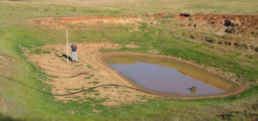 An empty dam with farmer holding depth measure